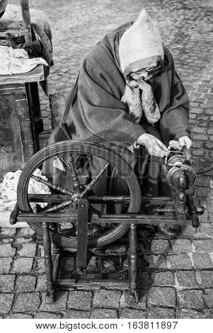 Trento Italy - January 3 2016: Elderly woman uses the cocoons of silkworms to spin using an old spinning wheel of wood.