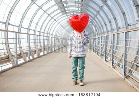 boy hid his face behind a red balloon. kid with a red balloon as an heart. the concept of Valentine's day. empty space for your text