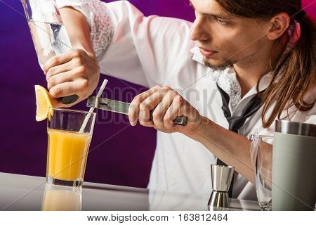 Alcohol liquor drinking party relax bartending concept. Young bartender pouring beverages. Male barman prepares cocktail in glass shaker.