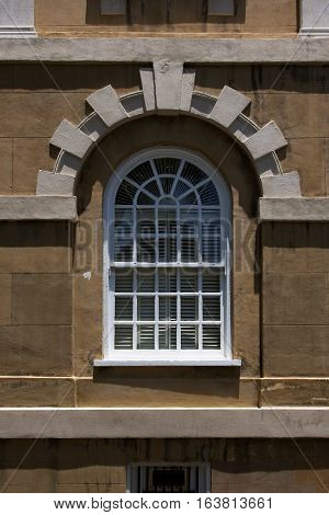 Ornate colonial style radius window with Voussoir stone arch on a historic building in downtown Charleston, South Carolina.
