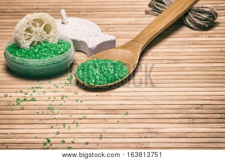 Natural products and accessories for peeling and exfoliation: sea salt, loofah, pumice on wooden surface. Copy space. Retro style processing