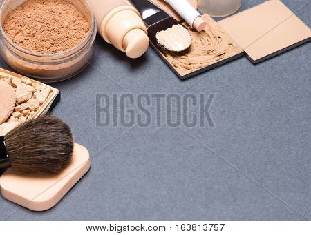 Beauty background. Frame of foundation makeup products with brushes and cosmetic sponges on gray surface