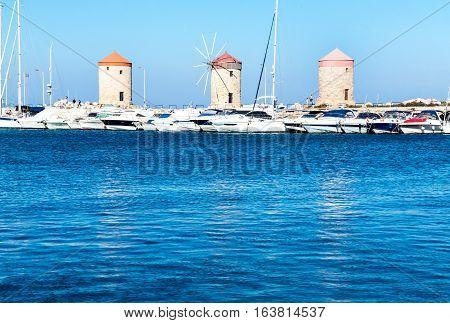 Three beautiful medieval Windmills of Mandraki Harbor in Rhodes as majestic reminders of times, Greece