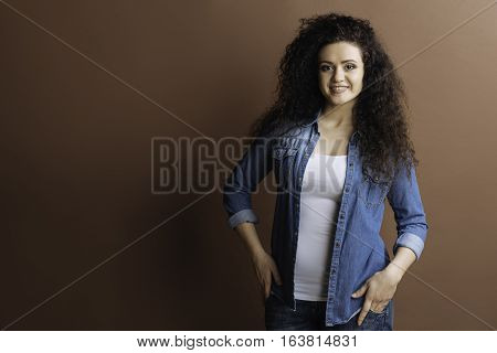 Casual style. Young woman with curly hair smiling holding both hands in jeans, looking at camera