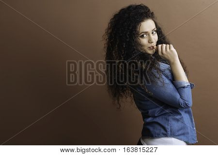 Have fun. Pretty female with curly hair standing in semi position turning head to the photographer keeping her finger in the mouth