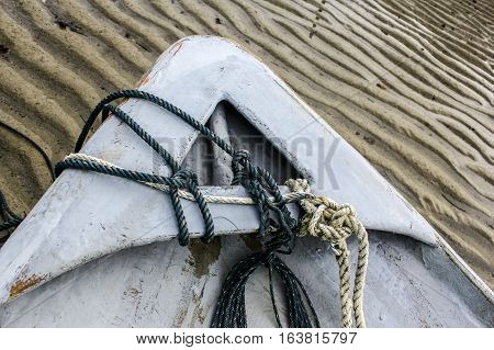 Ropes on fiberglass desk of fishing boat with background of low tide sand beach