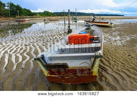 Fishing boats in Tanjung Aru jetty,Labuan island,Malaysia fishing village with blue sky and clouds at low tide.