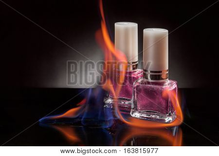 Nail polish bottle in a flame of fire on a black background
