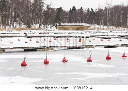 Many red marine buoys in frozen water in harbor in winter