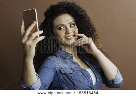 I like myself. Happy young woman holding her phone in right hand, looking at it while making photo