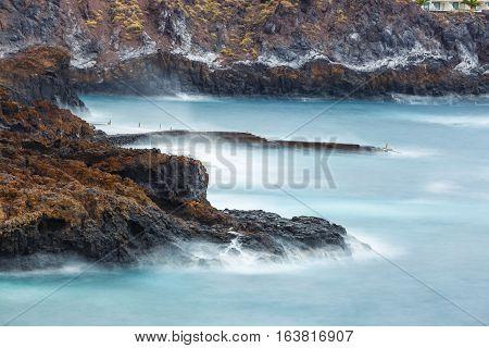 Blue Motion Blur Water Surrounding Rocks, Long Time Exposure