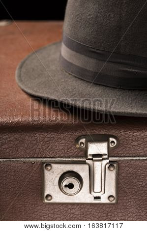 Travel and adventure concept. Vintage brown suitcase with vintage hat on black background.