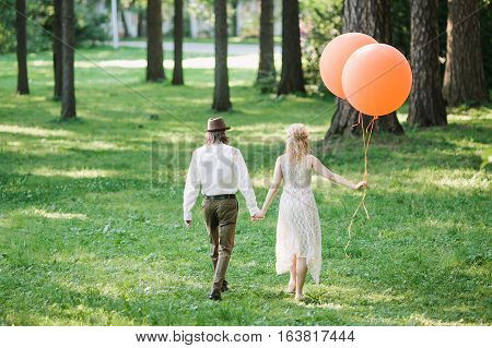 Newlyweds with orange balloons. Funny photo with newlyweds. The young couple leaves afar with balloons.