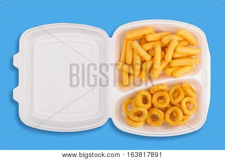 top view of junk food ingredients in a white take away packaging box on blue background calories concept