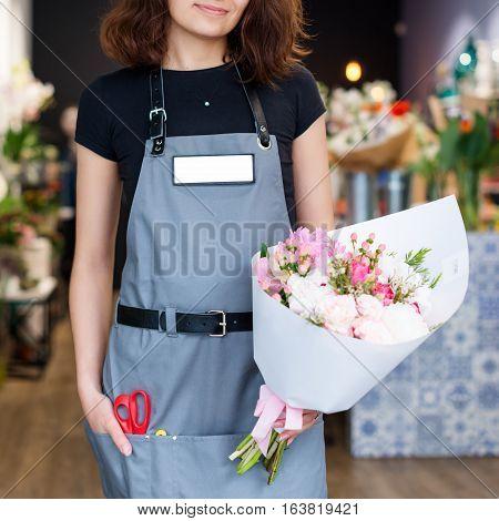 Florist hands showing bouquet of spring flowers. Selective focus