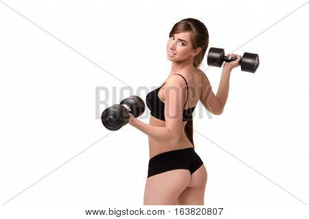 Girl with a beautiful figure shows the ass in a bikini. She is holding the dumbbells back to the viewer