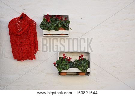Red handmade dress and two flower pots hanging on a white wall of a trullo in Alberobello, Apulia, Italy