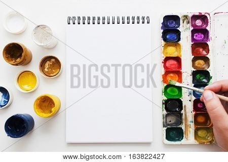 Artist painting with watercolor dye mockup flat lay. Top view on painter hand taking aquarelle paint in blank sketchbook. Art, workshop, painting, craft, creativity concept