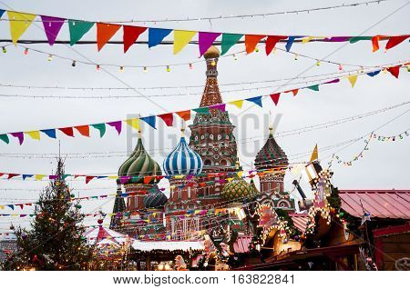 Moscow, Russia - December 29, 2016: Flags, lights, Cristmas tree and little houses roofs in front of the Cathedral of Vasily the Blessed