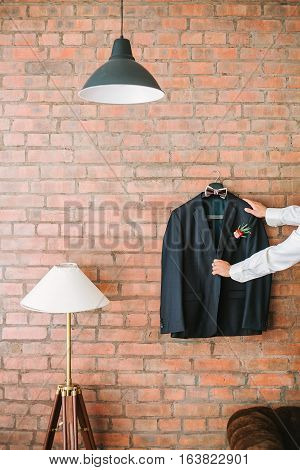 charges on the groom's wedding. the groom's jacket on a brick wall. Men's suit.