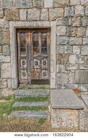 Brown old wooden door of the typical house in Tucepi village, Croatia.