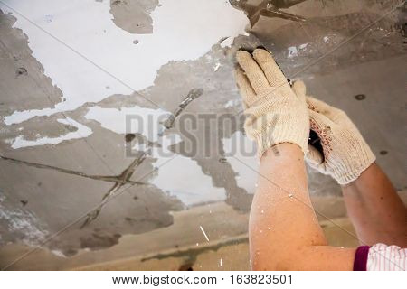 The worker scrapes the old paint on the ceiling. With a spatula work preparing the ceiling for painting