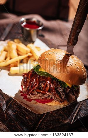 Tasty fast food. Close up of a burger being served with French fries and standing on a table while being cooked in restaurant.