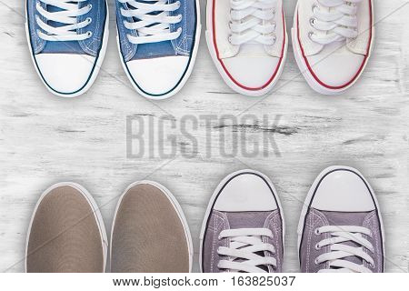 Top view Gray sneakers and blue sneakers and white sneakers other shoes on white wooden floor background,