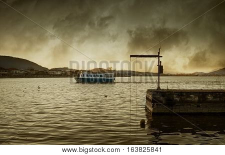 Dramatic lake. Scenic view of a dark and dramatic lake with a boat leaving the port. Ioannina. Greece