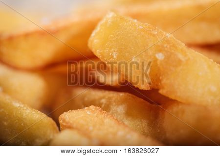 Traditional dish. Close up of tasty French fries being cooked in a restaurant and standing on a table.