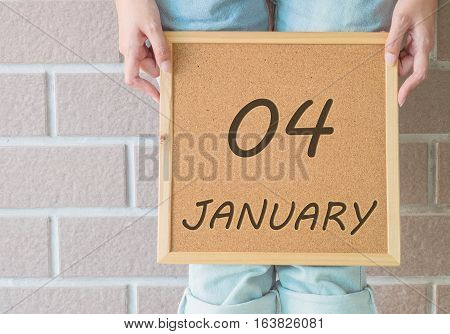 Closeup calendar at the cork board in hand of asian woman in front of her legs with 4 january word on brick wall textured background