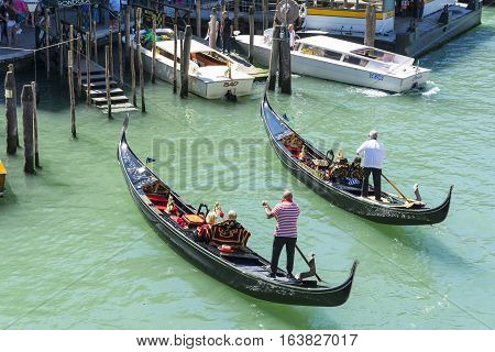 VENICE,ITALY-AUGUST 17,2014:two gondoliers lead tourists on a romantic trip on the canal in Venice during a summer day