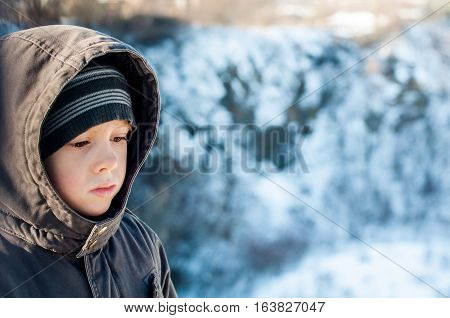 Portrait of sad lonely boy in winter