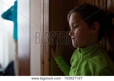Sad little boy at home. Standing near wooden wall. Dressed in a green fleece sweatshirt