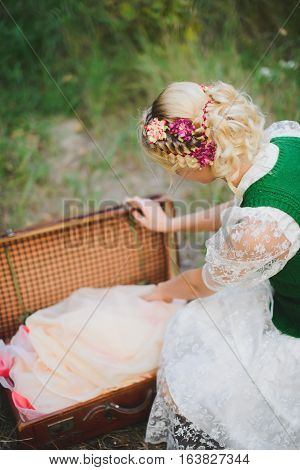 stylishly dressed girl closes the old chest