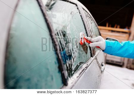 Woman Deicing Side Car Windshield With Scraper