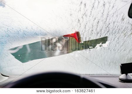 Woman Deicing Front Car Windshield With Scraper
