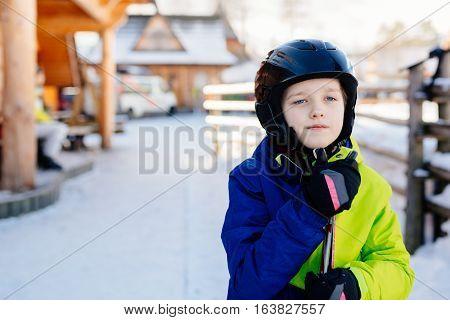 Child In A Black Ski Helmet Holding His Skis
