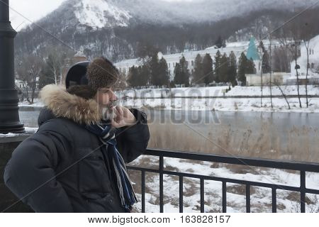 Mature bearded man on the waterfront of Sviatohirsk intently looking into the distance