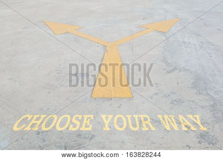 Closeup surface old and pale yellow painted arrow sign on cement street floor with choose your way word textured background