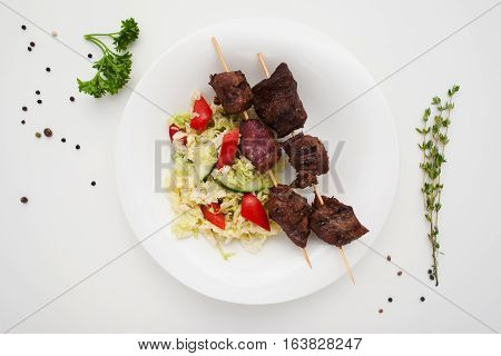Appetizing shashlik with salad on plate flat lay. Top view on grilled pork sticks served with fresh vegetables. Healthy food, dinner, menu concept