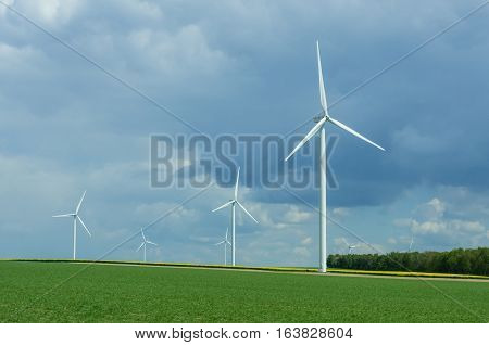 Rural landscape in France with blue sky and green field with spinning wind power stations producing environmentally friendly electric energy.