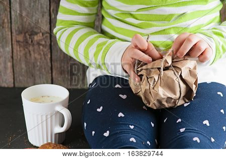 a Caucasian child girl unwraps kraft paper pulling a rope