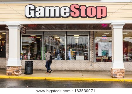 Fairfax, USA - November 30, 2016: Gamestop store facade exterior selling games with couple walking by