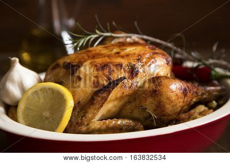 Roasted chicken with lemon and herbs in a ceramic dish