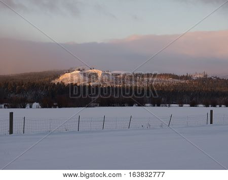 The foot hills of Central Oregon glow with the morning sun on a winter day with a fence and snow covered field in the foreground.