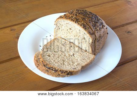 Sliced wholegrain bread lies on white plate on brown wooden surface. Photo closeup