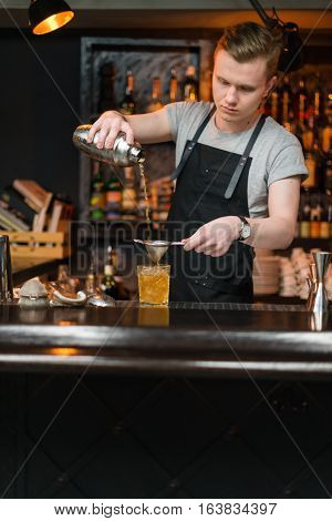 KIEV, UKRAINE - 30 OCTOBER, 2016: Barman festival. Young handsome bartender is making cocktail