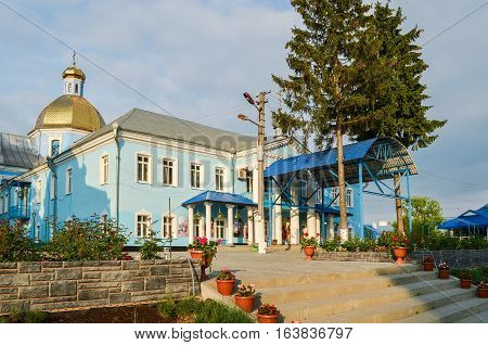 Gorodok, Ukraine - May 14, 2013: Blue colored orthodox church in small town in Rivne oblast or region with gold cupola and flower pots