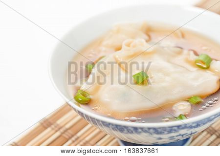 Bowl of wonton soup photographed closeup. Selective focus to the center of the bowl.